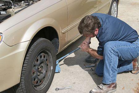 Een monteur met een aansluiting op te heffen van een auto en het verwijderen van de band. Stockfoto