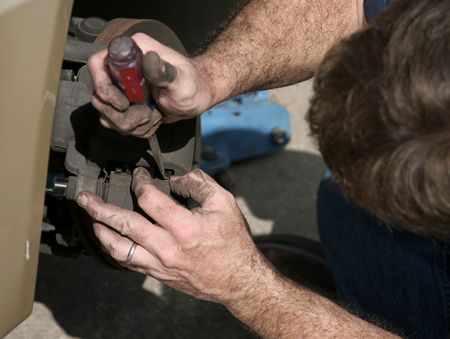 A mechanic opening the brake housing on a car to check the brake pads. photo