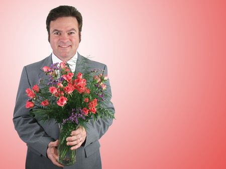 A handsome husband in a suit holding a bouquet of pink sweetheart roses over a pink packground. Stock Photo - 356151
