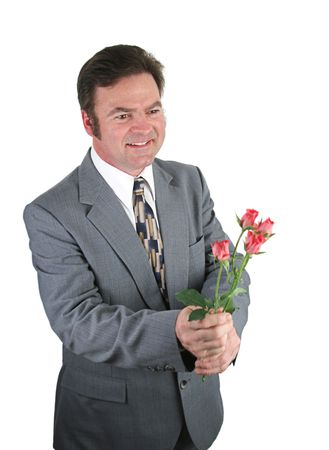 A handsome man in a suit bringing roses for his date.