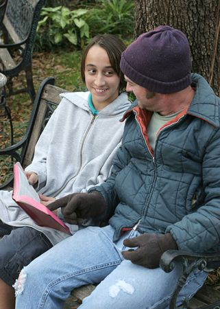 A teenaged volunteer explaining the bible to a homeless man. Imagens