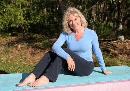 A beautiful, mature woman relaxing after doing yoga outdoors. Stock Photo