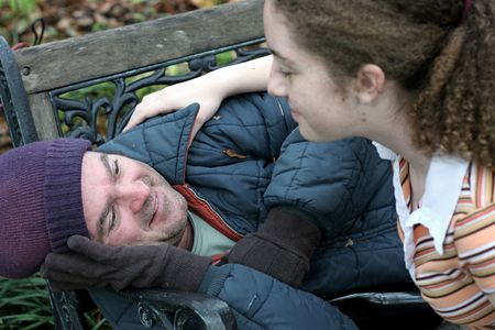 A homeless man being helped by a teen volunteer. (focus on homeless man's eyes) Stockfoto