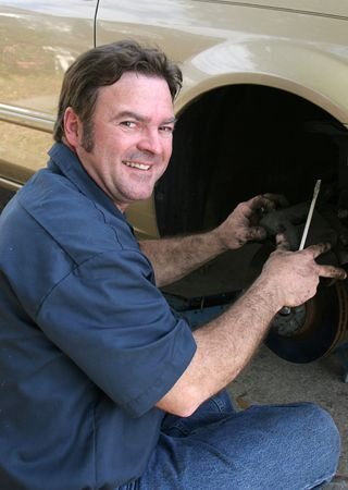 trustworthy: An honest looking, trustworthy mechanic repairing a car. Stock Photo