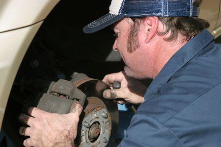 An auto mechanic working on brakes.