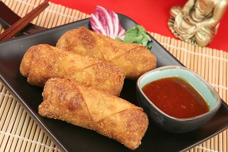 A plate of crispy fried egg rolls with spicy sweet chili sauce for dipping. photo