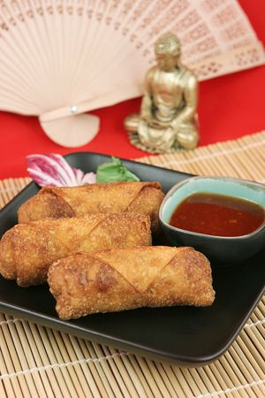 A plate of crispy egg rolls displayed in front of a Buddha and a Chinese fan. Stock Photo - 384538