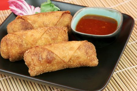 tangy: Crispy Chinese egg rolls with sweet, tangy chili sauce for dipping.