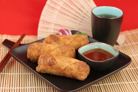 Crispy fried egg rolls with dipping sauce, served on a bamboo mat with tea.