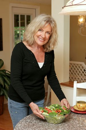 roughage: A beautiful, mature woman serving a healthy green salad.