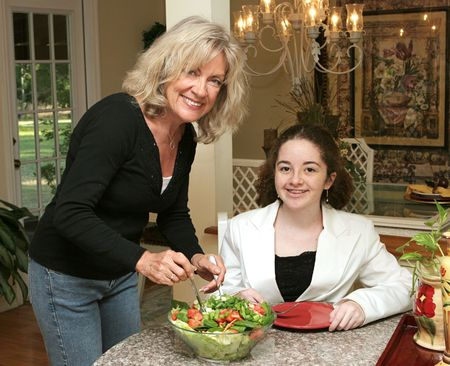 roughage: A mature woman serving healthy salad to a guest.