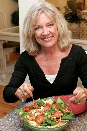 midlife: A beautiful woman in her fifties staying fit by eating healthy. Stock Photo