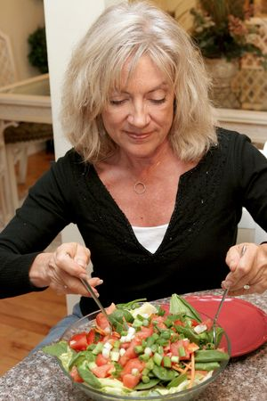 roughage: A beautiful fit woman in her fifties eating a healthy salad. Stock Photo