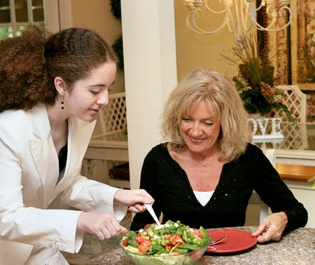 roughage: A teen girl and a mature woman eating a healthy salad for lunch.