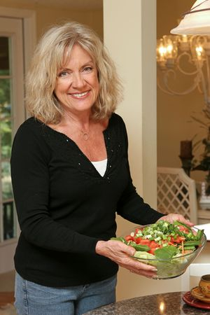 A beautiful, mature woman with serving a healthy green salad. photo