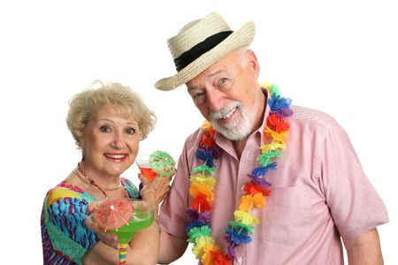 An attractive elderly couple on a tropical vacation, drinking cocktails. Stock Photo - 388954