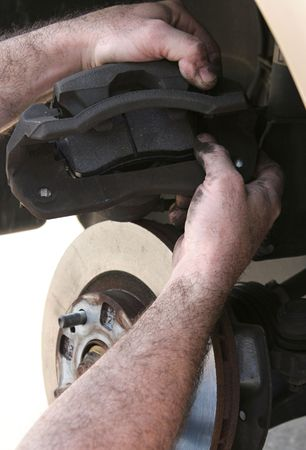 brake caliper: A mechanics hands inserting new brake pads in the caliper. Stock Photo