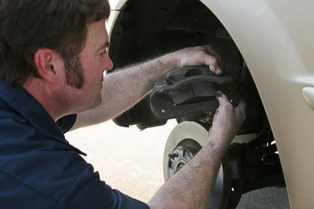 An auto mechanic working on disc brakes,  inserting new brake pads in the caliper. Stock Photo