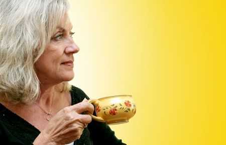 applied: A beautiful mature woman enjoying a cup of coffee as the sun comes up.  Golden background with gradient applied. Stock Photo