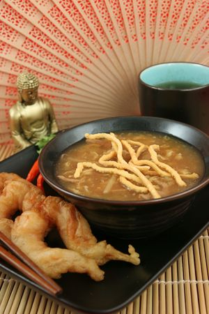 A steaming bowl of hot & sour soup and golden fried fantail shrimp served at a Chinese restaurant.