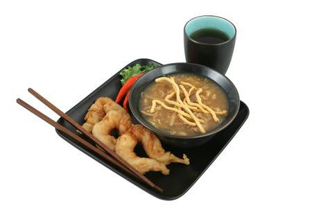 A bowl of Chinese hot & sour soup with crunchy noodles and golden fried fantail shrimp served with tea.  Clipping path included.