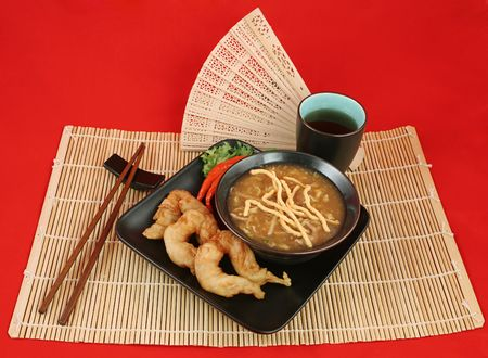 fantail: A delicious chinese dinner of hot & sour soup, fried fantail shrimp on a bamboo mat.  Complete meal with chopsticks & tea over red. Stock Photo