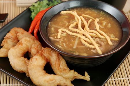 Chinese hot & sour soup served with fried shrimp and crunchy noodles.  Closeup view. Stock Photo - 400189