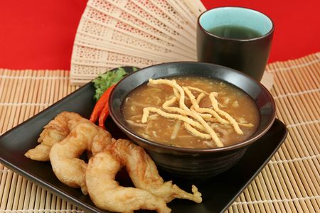 fantail: A bowl of hot & sour soup with chow mein noodles, fried fantail shrimp and hot tea.