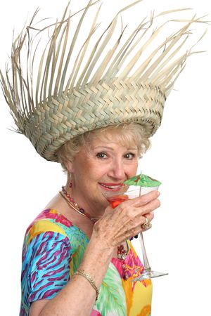 maturity: A beautiful senior lady enjoying a tropical cocktail on a cruise.  Isolated. Stock Photo