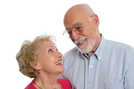 maturity: A happy senior couple sharing a private joke together.  She is wearing a hearing aid.  Isolated. Stock Photo