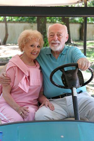 A loving senior couple in a golf cart.