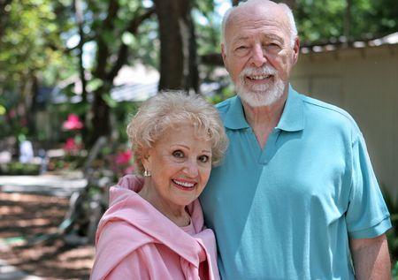 An active senior couple walking through their garden.  Horizontal with room for text. Stock Photo - 418724