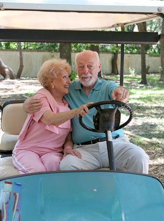 he and she: A senior couple riding in a golf card.  She is steering and he is pointing where to go.