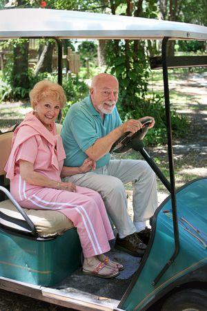 An active senior couple driving a golf cart. Stock Photo - 418722