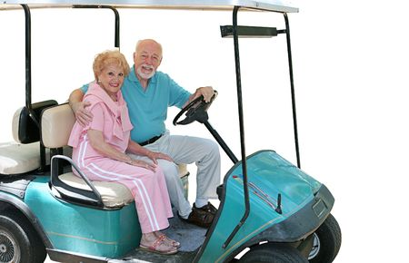 An attractive senior couple in a golf cart.  Isolated. photo
