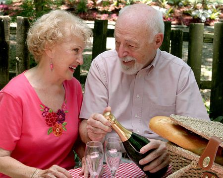 An attractive senior couple on a picnic, looking lovingly into eachothers eyes as he opens the wine. photo
