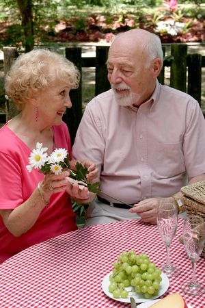 A romantic senior man giving his wife flowers while they are on a picnic. photo