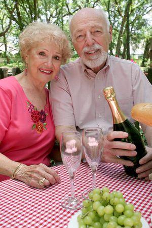 An attractive senior couple enjoying a picnic in the park. photo