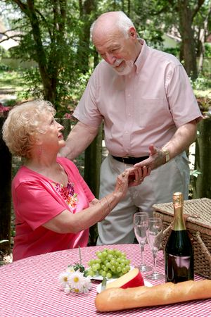 A senior husband surprises his wife with a romantic picnic for two. photo