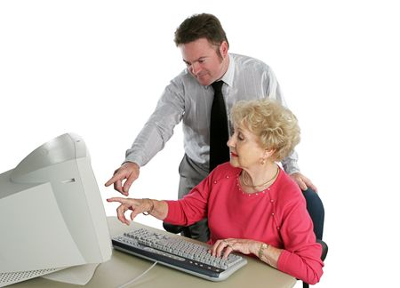 A senior lady taking computer lessons from an instructor. photo