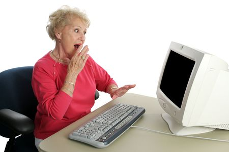 A senior woman viewing shocking internet content.  Screen intentionally blank, ready for text or image. photo