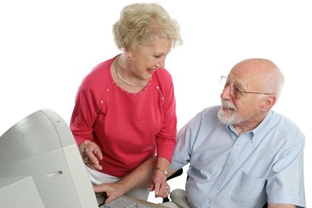 An attractive retired couple surfing the net together. Isolated photo