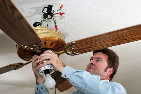 ceiling fan: An electrician removing an old ceiling fan.  The fan was installed without a ceiling box, in violation of code. Stock Photo