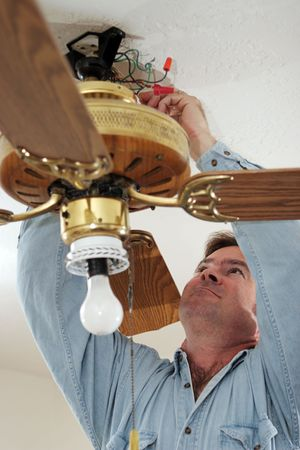 An electrician disconnecting the wires of an old ceiling fan.  Fan was installed without ceiling box - a code violation.  Model is a licensed master electrician, actually performing the work. photo