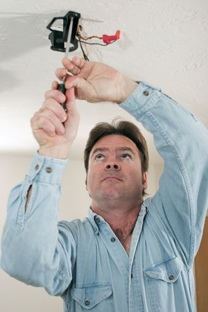 ceiling fan: An electrician unscrewing a ceiling fan assembly which is not attached to a ceiling box, in violation of code.  Model is a licensed master electrician actually performing the work.