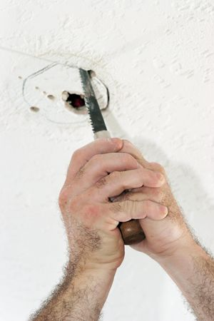 An electrician with using a saw to cut a hole in the ceiling to put a fan box. Work is being performed by a licensed master electrician. photo