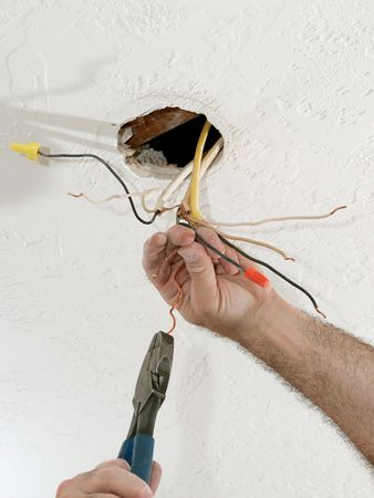licensed: A closeup of an electricians hands as he uses pliers to straighten electrical wires.  Work is being performed to code by a licensed master electrician.