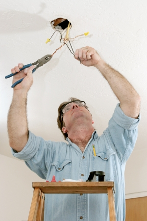 licensed: An electrician on a ladder using a pliers to separate wire.  Work is being done to code by a licensed master electrician. Stock Photo