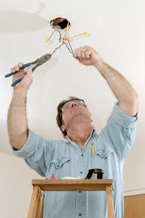 alicates: Un electricista en una escalera usando un cable de pinzas para separar. Se est� trabajando en el c�digo de licencia por un maestro electricista.