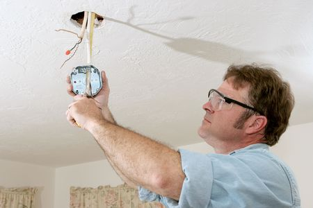 An electrician pulling wires through a ceiling fan box.  Work is being performed to code by a licensed master electrician.